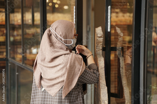 Muslim women are opening the glass doors of the cafe using their elbows in accordance with health protocols, the woman is wearing a medical cloth mask to prevent transmission of the virus Canvas Print