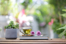 Green Tea In Transparent Glass With Flower And Succulent Plant Pot With Notebook On Wooden Table At Outdoor
