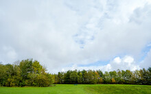Beautiful Natural Landscape Meadow At Public Park With Could And Blue Sky In Spring Or Summer. Fresh Air Panorama View Of Grass Field With Metal Bench On Green Forest Trees Environment