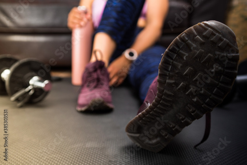 Young woman resting at home after doing exercise at home. Close up footwear, girl picking up the water bottle.