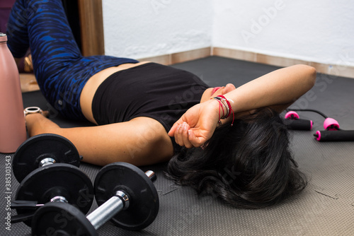 Young tired girl resting on the floor after exercising at home. Concept of healthy and sport with dumbbell and jump rope.