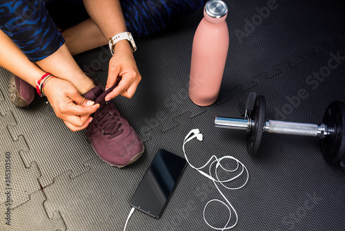 Detail of woman tying footwear to do exercise. Black rubber floor mat and tiles inside a gym. Technology sport with smart phone and earphones.