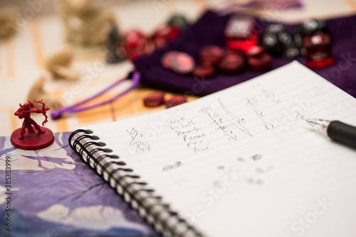 Set of pen, notebook, tokens and dices to play role game like dungeons and dragons.