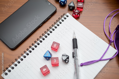 Set of pen, notebook, smart phone and dices to play role game like dungeons and dragons.