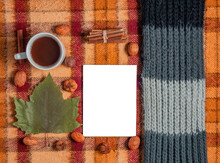 Old Checkered Blanket With Orange Red And Brown Patterns. Dry Leaves And Fruits. Autumn Background. Plain White Sheet Of Paper. Cozy Woolly Gray Scarf. Cup Of Coffee.
