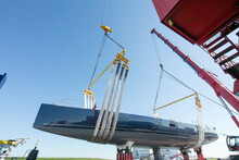 Launch Of A Super Sailing Yacht. Lifting And Hoisting With Cranes. Shipbuilding Industry.