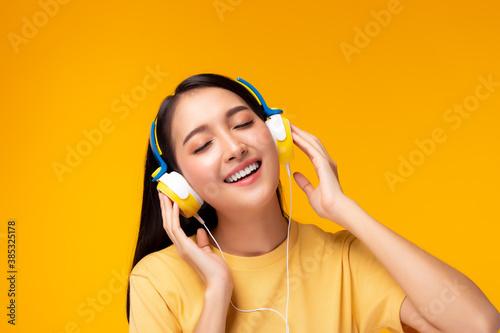 Fototapeta Beautiful asian woman listening music in headphones with smile face