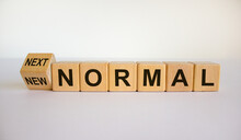 Turned A Cube And Changed The Words 'new Normal' To 'next Normal'. Covid-19 Postpandemic Concept. Beautiful White Background, Copy Space.
