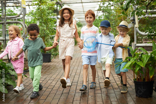 Photo older sister with younger brother and sisters on excursion in the garden