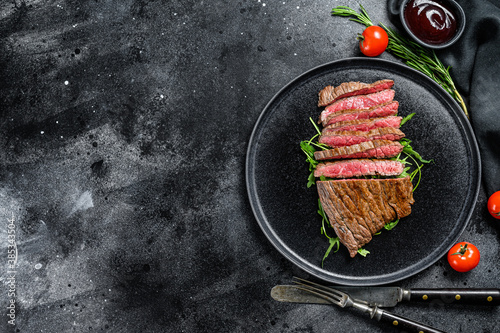 Fototapeta Grilled and cut flank steak. Marble beef meat. Black background. Top view. Copy space obraz