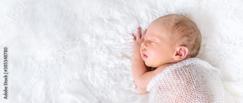 Obraz na plátně Newborn baby sleeping on a white background. Selective focus.