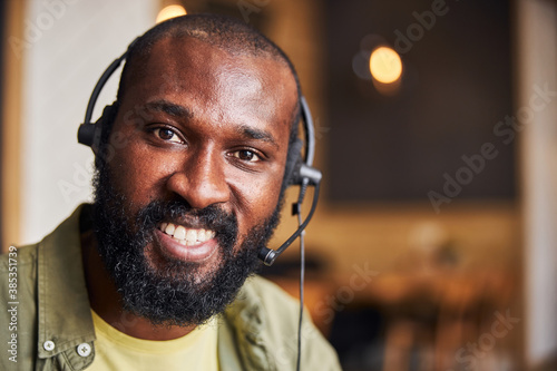 Photo Handsome Afro American man in headphones expressing positive emotions