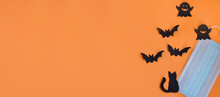 Top View Of Medical Protective Mask, Silhouette Of Black Bats, Ghosts, Cat On Orange Background. Halloween , COVID-19 Prevention And New Normal Concept. Flat Lay.Banner