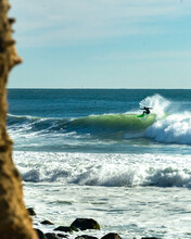 A Surfer Carves Down The Face ...