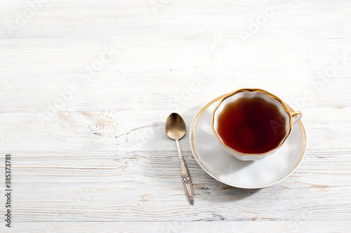 A porcelain cup with tea on long empty table. Space for text. Wallpaper Mural