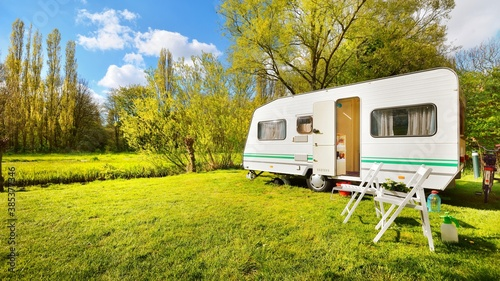 Obraz Caravan trailer on a green lawn, on a sunny spring day. Transportation, vacations, weekend, road trip, home, alternative lifestyle, leisure activity, camping - fototapety do salonu