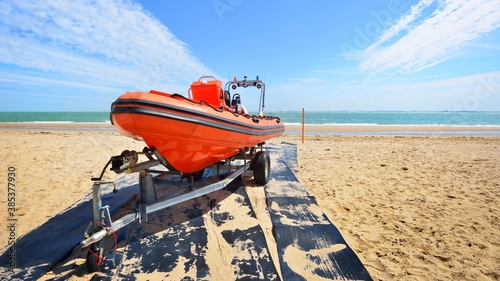 Obraz Red patrol lifeguard boat loaded on a trailer at the beach on a sunny day - fototapety do salonu