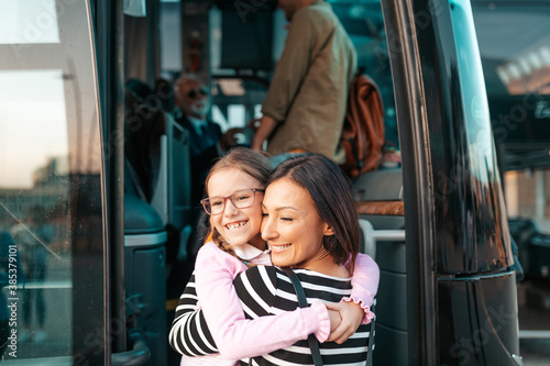 Fotomural A mother hugs her daughter in front of the bus before her trip.