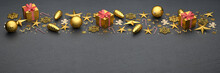 Flat Lay Golden Christmas Ornaments And Sweets On A Black Stone Plate. Banner Size With Copy Space On The Bottom.