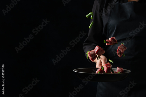 The professional chef tossed fresh pork with asparagus in frying pan on black background Fototapet