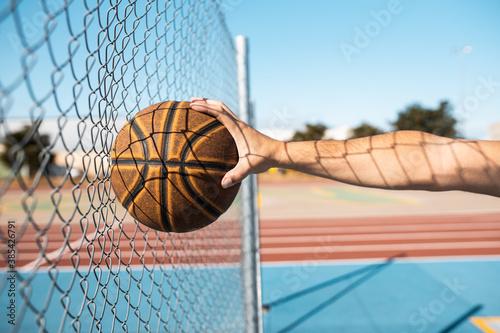 Fotografiet man playing basketball an outdoor court on the street.