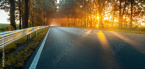 Obraz Herbstliche Landstraße bei Sonnenaufgang - fototapety do salonu