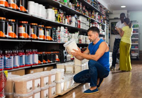 Fototapeta Portrait of interested sports man choosing food supplements in large assortment of sport nutrition shop obraz