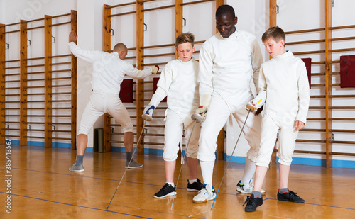 Obraz Coach demonstrating to teenage athletes stances and movements with rapier during fencing workout - fototapety do salonu