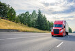 canvas print picture - Red big rig semi truck with black grille transporting cargo in semi trailer driving on the straight wide highway road with trees on the hillside