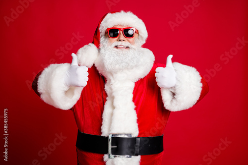 Portrait of his he nice handsome content glad cheerful cheery bearded Santa showing two double thumbup cool agree deal done isolated over bright vivid shine vibrant red color background
