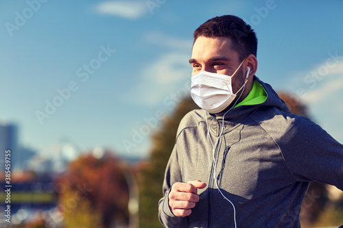 fitness, sport and health concept - man wearing face protective medical mask for protection from virus disease running and listening to music in earphones at city