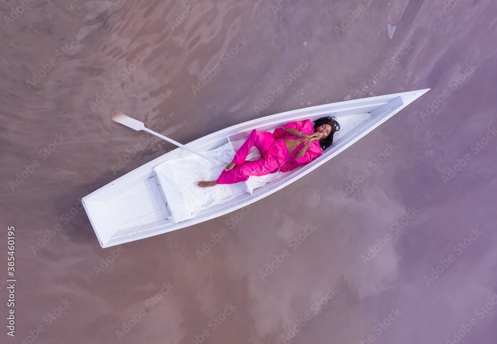Fototapeta Amazing dream fairy fabulous fantasy style composition black woman in pink suit lying white boat and looking up camera. Aerial drone artistic creative conceptual imagination subconscious psychotherapy