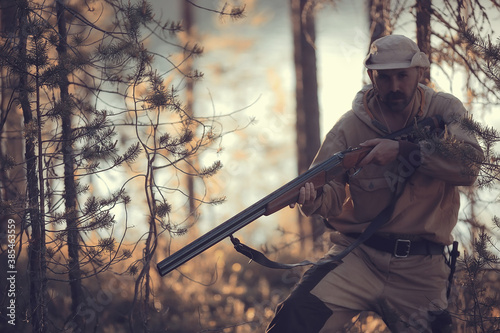 hunting man / hunter with a gun hunting in the autumn forest, yellow trees lands Fototapet