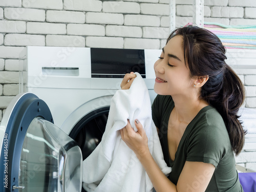 Photo Asian woman in laundry room.