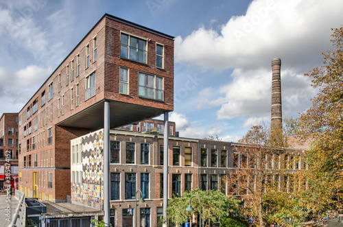 Delft, The Netherlands, October 4, 2020: Modern brick housing block partially build over a row of hundred years old townhouses