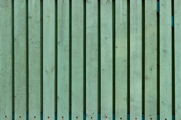 The surface of old wooden planks with peeling green paint.