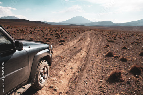 Fototapeta Off-road vehicle on dirt road leading to mountains