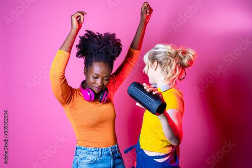 Young beautiful black and cacuasian women dancing indoor on pink baground holding wireless speaker  - Two isolated diverse female friends clubbing