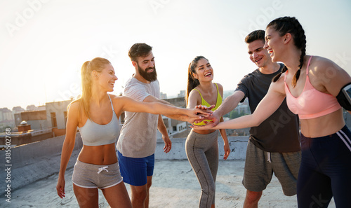 Group of cheerful fit fitness team exercising together outdoor
