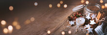 Christmas Decoration With Cinnamon Stars, Baking Ingredients. And Candlelight On Wood. Horizontal Background With Atmospheric Bokeh For Christmas Dekoration And Space For Text.
