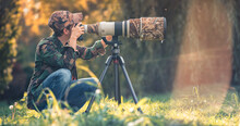 Wildlife Photographer Using Telephoto Lens With Camouflage Coating Photographing Wild Life Using Gimbal Head On Tripod. Professional Photography Equipment For Cinematic Shooting In The Nature Outdoor