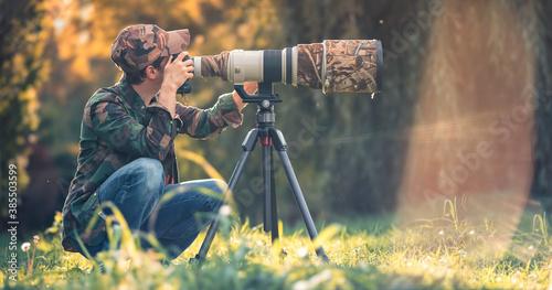 wildlife photographer using telephoto lens with camouflage coating photographing wild life using gimbal head on tripod Fotobehang