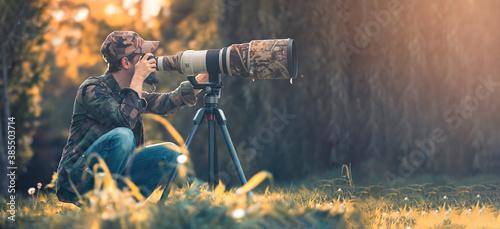 wildlife photographer using telephoto lens with camouflage coating photographing wild life using gimbal head on tripod Canvas