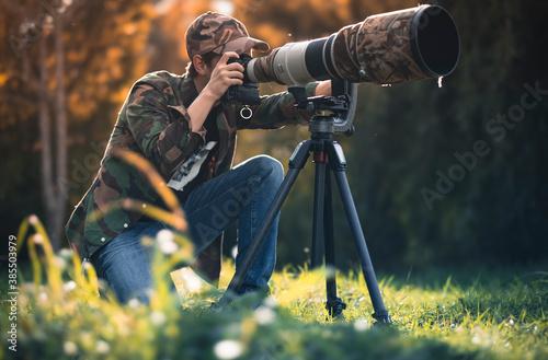 Fotografia wildlife photographer using telephoto lens with camouflage coating photographing wild life using gimbal head on tripod