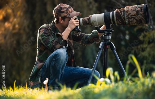 Tela wildlife photographer using telephoto lens with camouflage coating photographing wild life using gimbal head on tripod