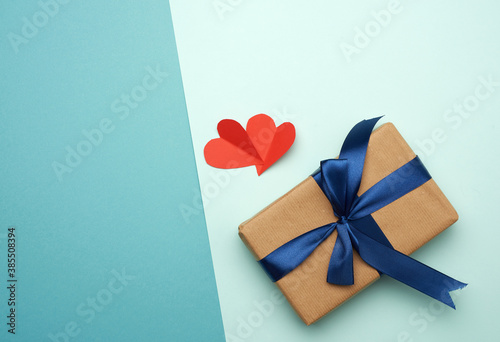 box wrapped in brown paper and tied with a blue silk ribbon with a bow Fotobehang