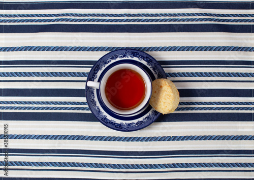 Obraz A cup of tea with a cookie in the center on a striped tablecloth; cenital plane - fototapety do salonu