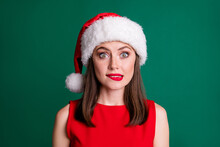 My Fault. Closeup Photo Of Attractive Charming Terrified Lady Bite Lips Late With Party Decorations Oh No Santa Will Scold Me Wear X-mas Cap Red Dress Isolated Green Pastel Color Background