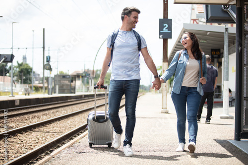 Obraz traveler couple backpacker tourist together at train station - fototapety do salonu