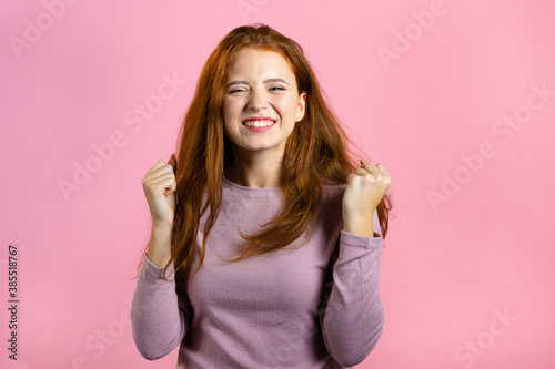 Fotomural Woman with red hair very glad and happy, she shows yes gesture of victory, she achieved result, goals